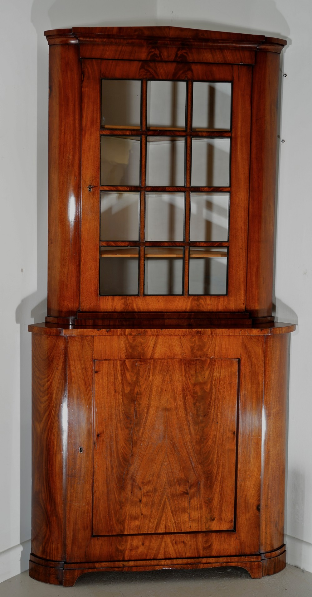 a highly figured mahogany two piece corner cabinet cupboard